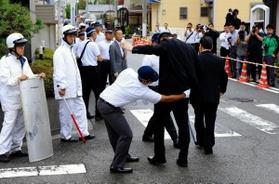 定例会に集まった任侠山口組の組員にボディーチェックをする兵庫県警の捜査員=2018年9月、尼崎市東難波町4