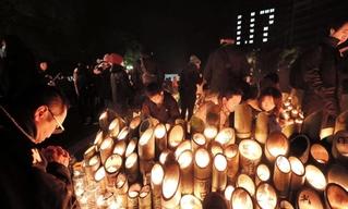 明かりに照らされる竹灯ろうの前で祈りを捧げる人たち=17日午前6時13分、神戸市中央区、東遊園地