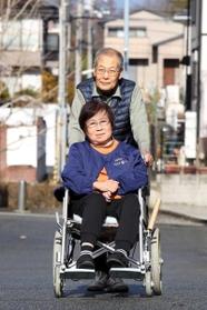 夫の雅男さんに押してもらいながら、車いすで近所を散歩する村田延子さん=神戸市北区鹿の子台(撮影?風斗雅博)